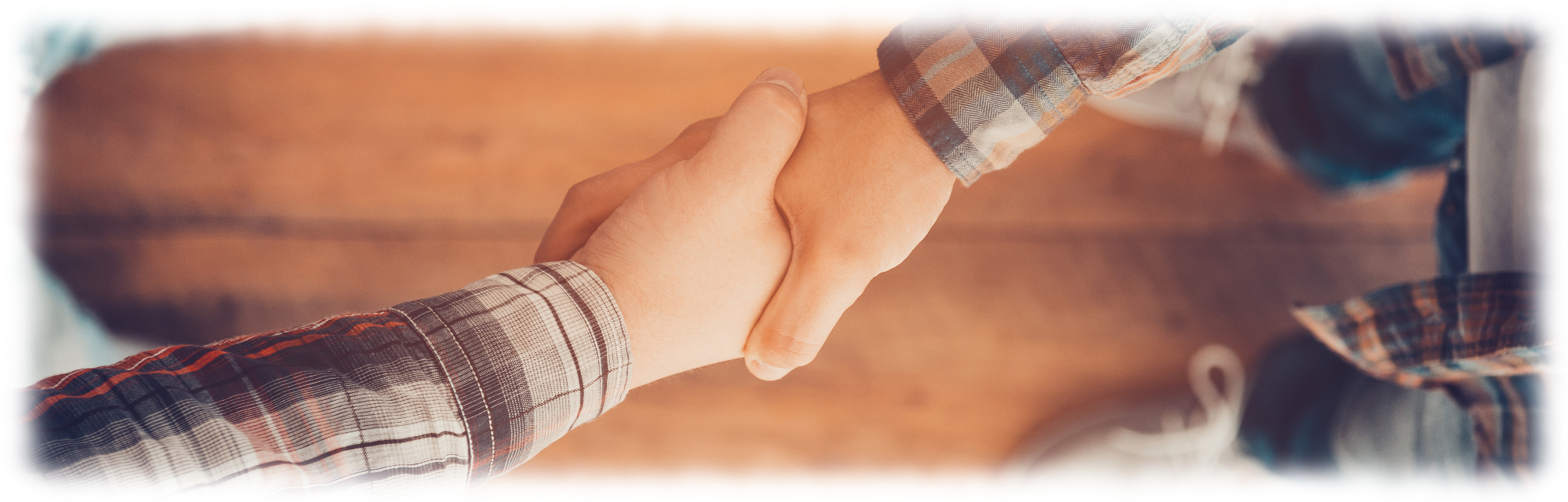 two men shaking hands over hardwood floor